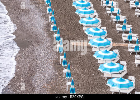 Rows of blue and white parasols and sunbeds on the beach at Atrani on the Amalfi Coast, Italy. - Stock Photo