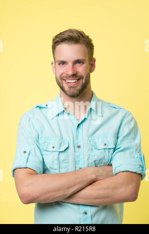 Cheerful consultant. Man smiling face posing confidently with folded arms yellow background. Man shop consultant looks cheerful confident and hospitable. Guy with bristle glad to help you in shop. - Stock Photo