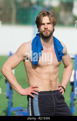 Taking minute break. Man athlete with shirt on shoulders after training outdoor. Athletic man relaxing break. Athlete muscular torso takes break during exhausting training. Sportsman workout outdoor. - Stock Photo