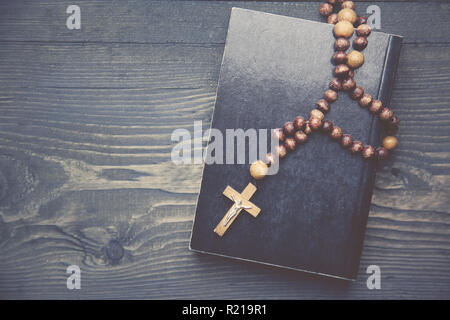 cross on book on wooden table - Stock Photo