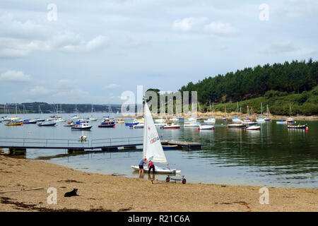 St Just in Roseland, UK - 25th July 2017: A calm summer morning brings two people out to prepare their small boat on the creek at St Just in Roseland on the picturesque Roseland Peninsula in Cornwall, UK - Stock Photo