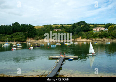 St Just in Roseland, UK - 25th July 2017: A calm summer morning brings people out to their small boats on the creek at St Just in Roseland on the picturesque Roseland Peninsula in Cornwall, UK - Stock Photo