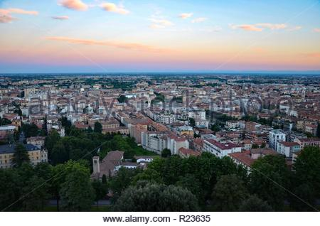 Bergamo in Lombardy in Italy at sunset, view from the cable railway station towards the lower town, summer - Stock Photo