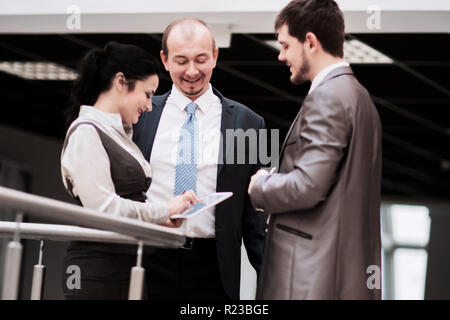 smiling business team discussing something in the office - Stock Photo