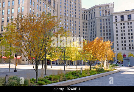 Fall tree foliage on downtown Cleveland Public Square in front of Tower City Center, part of the Landmark Office Towers Complex in Cleveland, Ohio, US - Stock Photo