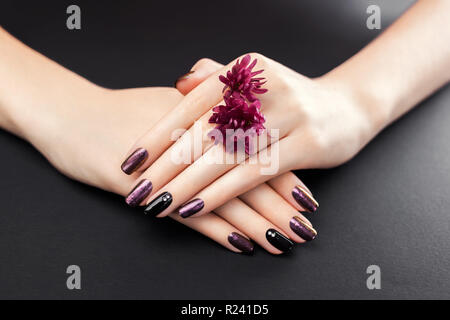 Black and burgundy manicure with flowers on black background. Gel nail polish with mirror powder pigment. Body care - Stock Photo