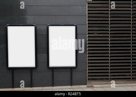 Two blank billboards for advertising, against a black wall - Stock Photo