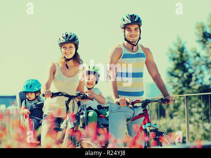 Happy smiling family with two little daughters traveling by bicycles - Stock Photo