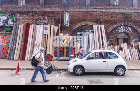 Pedestrians walk past carpets for sale at Sclater Street Fleat Market in the East End of London. - Stock Photo