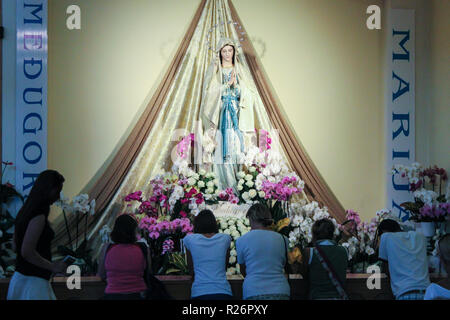 Medjugorje August 2013. Parishioners & pilgrims pray in front of a statue of Our Lady in the church of St James. - Stock Photo