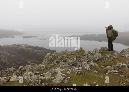 Single photographer taking photo of landscape in the mist, Fair Isle, Shetland Islands - Stock Photo