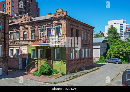 Older two-storey houses of the late 18th century in downtown against background of new high-rise buildings - Stock Photo
