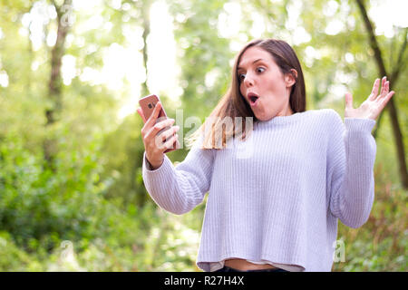 European young brunette woman very surprised looking towards the mobil new job offers in nature or forest - Stock Photo