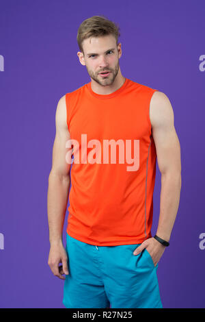 Athlete on violet background. Muscular man in orange vest and blue shorts, sportswear fashion. Fit and confident. Sport fashion for training and workout. Fitness and wellness. - Stock Photo