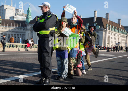 London, UK. 17th November, 2018. Clowns from Clandestine Insurgent Rebel Clown Army (CIRCA) support Extinction Rebellion blocking Westminster Bridge, one of five bridges blocked in central London, as part of a Rebellion Day event to highlight 'criminal inaction in the face of climate change catastrophe and ecological collapse' by the UK Government as part of a programme of civil disobedience during which scores of campaigners have been arrested. Credit: Mark Kerrison/Alamy Live News - Stock Photo