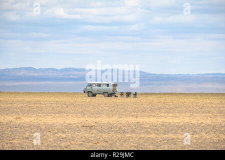 Russian made van parked with a few lazy chairs laid out for a relaxing day to watch the day passes by in the middle of Gobi desert. - Stock Photo
