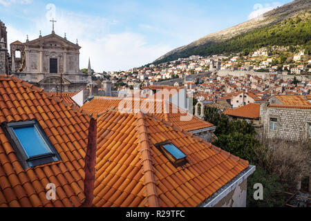 View over the roofs of Dubrovnik and church St. Stepan with bell tower with green mountain in the background, Croatia - Stock Photo
