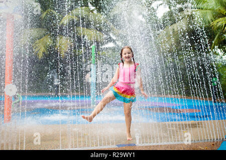 Kids play in aqua park. Children at water playground of tropical amusement park. Little girl at swimming pool. Child playing at water slide on summer  - Stock Photo