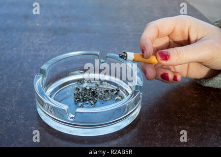 Hand holding cigarette next to ashtray - Stock Photo