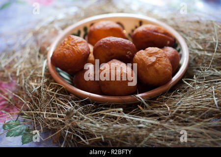 Ukrainian Donuts in a decorative bowl. Donuts on the table covered with hay - Stock Photo