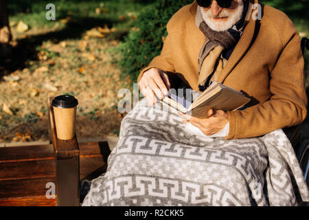 cropped shot of senior disabled man in wheelchair reading book on street - Stock Photo