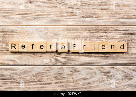 refer a friend word written on wood block. refer a friend text on table, concept. - Stock Photo