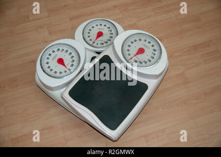 Dieting, weight loss and body image conceptual image of three analogue scales stacked one on top of the other - Stock Photo