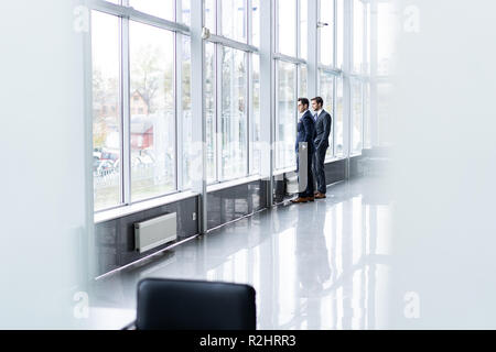 Two Businessmen Having Informal Meeting In Office Corridor - Stock Photo