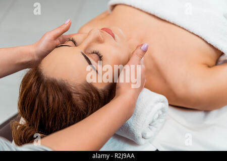 cropped shot of young woman having facial massage in spa salon - Stock Photo