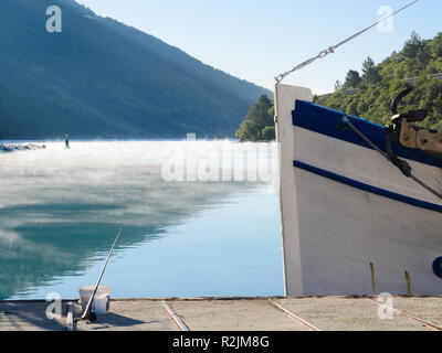 Small fishing boat bow docked with morning mist on the sea in a distance - Stock Photo