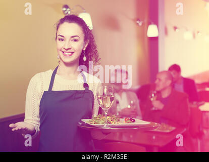 Young waitress greeting customers at table in restaurant - Stock Photo