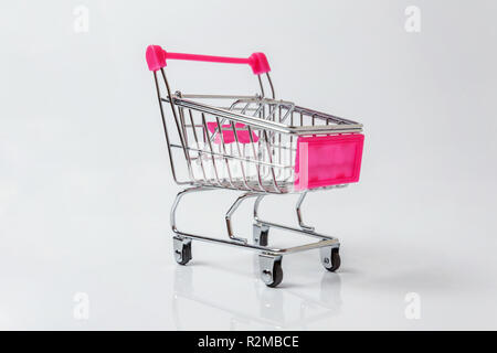 Small supermarket grocery push cart for shopping toy with wheels isolated on white background. Sale buy mall market shop consumer concept. Copy space - Stock Photo