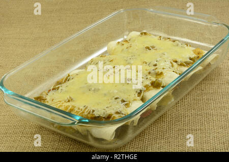 Baked chicken and bean enchildas smothered in salsa verde and cheese in glass baking dish - Stock Photo