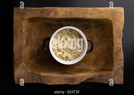 Breakfast on a wooden rectangular bowl with a black and white pot. - Stock Photo