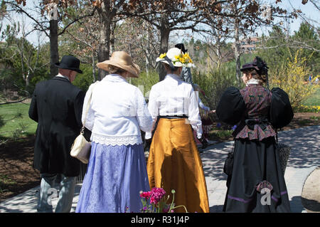 Two couples dressed up in vintage clothes walking down a path from behind. - Stock Photo