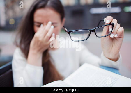 Closeup portrait of attractive female with eyeglasses in hand. Poor young girl has issues with vision. She rubs her nose and eyes out of fatigue. A student tired to study and read books - Stock Photo