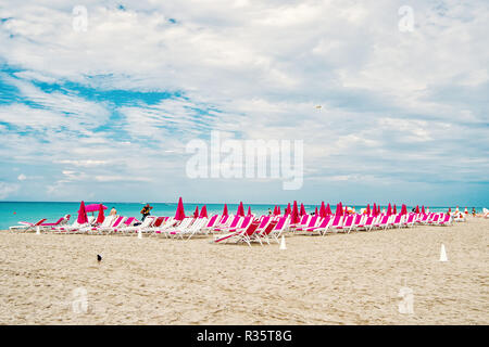 Miami, South beach. sandy beach with sunbeds, chairs and folded, pink umbrellas on blue sea or ocean coast on sunny cloudy sky. Idyllic summer vacation. Lounge and leisure - Stock Photo