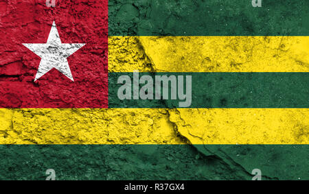 Flag of Togo close up painted on a cracked wall, concept of armed actions and conflicts in the world - Stock Photo