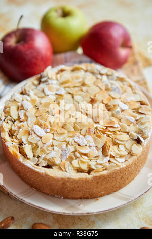 Freshly baked homemade apple pie with almond flakes cake on yellow - Stock Photo