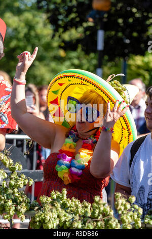 Faversham Hop Festival 2018. Mature woman in audience wearing inflatable yellow Mexican sombrero, and over large sunglasses, singing along. - Stock Photo