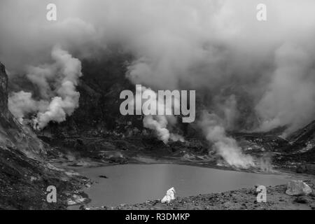 A lake on White Isalnd, New Zealand with smoke rising from it in black and white - Stock Photo