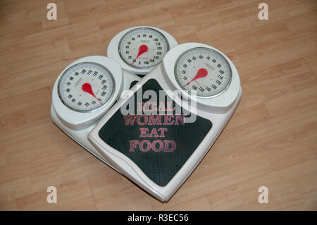 Dieting, weight loss and body image conceptual image of three analogue scales stacked one on top of the other with the text of 'Real Women eat food' - Stock Photo