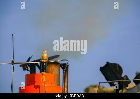 exhaust pipe emitting smoke and fumes from an old maritime diesel engine on a fishing boat - Stock Photo