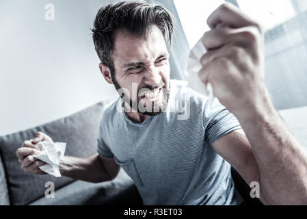 Show you strength. Negative delighted male person making fists while holding paper in hands, looking aside - Stock Photo