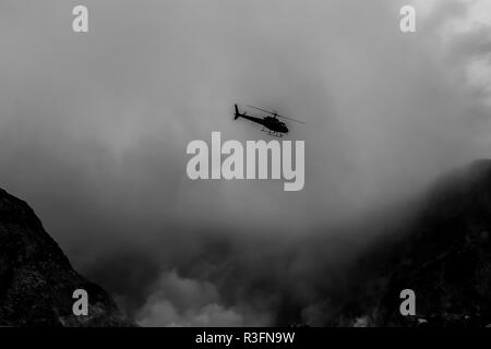 A helicopter flying through the smoke on White Island, New Zealand - Stock Photo