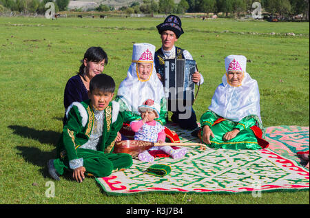 Kazakh family in traditional clothes listening to the music of an accordion player, Sati village, Tien Shan Mountains - Stock Photo