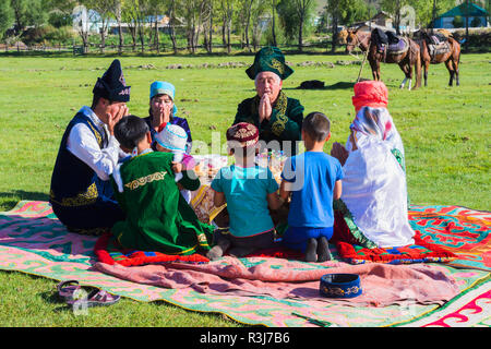 Kazakh family in traditional clothes praying before lunch, Sati village, Tien Shan Mountains, Kazakhstan - Stock Photo