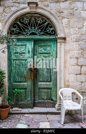 White plastic chair in front of locked with padlocks and chain old green damaged wooden doors in one of the buildings in Kotor, Montenegro - Stock Photo