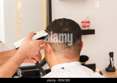 Back view of man getting short hair trimming at barber shop with a clipper machine - Stock Photo
