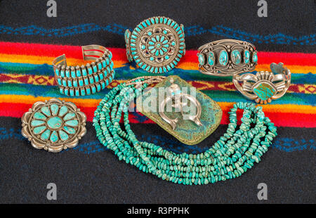 Collection of Native American Jewelry on a Colorful Textile Background. Turquoise and Sterling Silver Necklace, Bracelets and Pendants. - Stock Photo